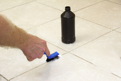 Hand with a blue handled black scrub brush cleaning grout with baking soda and peroxide. Floor grout tile being cleaned with baking soda and hydrogen peroxide.